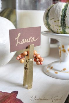 An easy and inexpensive way to decorate your Thanksgiving tabletop, simply spray-paint clothespins and glue faux berries for a pop of autumnal color.