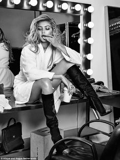 Sexy: She wears a pair of knee high boots as she poses in her dressing room in a white towelling robe
