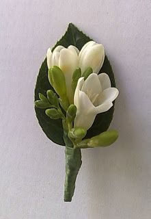 Freesia boutonniere... we would use lavender colored freesia instead of white.