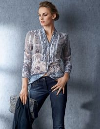 Beautifully printed permanent crinkle fabric in a meticulous, detailed finish with ruffled sections and strips of lace. Casual longer length with dainty stand-up collar, V-neckline and full-length button placket from chest height.