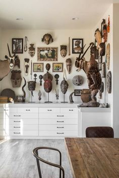 Tribal masks and artwork from the homeowners' collection are hung en masse above streamlined custom drawers built by Tharp Cabinet Company in the studio. The flooring is from Bedrosians Tile & Stone. African Interior Design, Arte Tribal, Tribal Art, African Furniture, African Home Decor, Ethnic Decor, Wall Decor, Room Decor, Interior Decorating