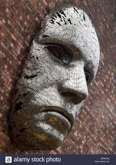Stock Photo - Metal face sculpture on the outside wall of the Lincoln City Drill Hall, Lincolnshire England UK