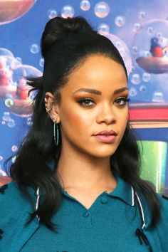 Rihanna's half-up is a far cry from your typical 'sides up' style, as is her way. Brush back half of your hair and secure the ponytail at the back of your crown. Wrap a second elastic around the tail, but loop it through, leaving half of the ends flipped out. Curl the bottom half of your hair with a large barrel and comb through to soften the style. GETTY