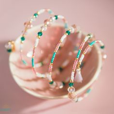 Riviera embodies the sparkling turquoise waters and peachy sunsets of the Mediterranean. The spiral bangle is made with radiant 22K Gold Plated beads, beautiful glass crystal beads and fine glass seed beads in shades of turquoise, coral pink and white.