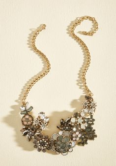 Each time you clasp the golden curb chain of this statement necklace at your nape, you're making a promise to fill the air with flair! Clusters of white, pale purple, smoke, and clear gemstones form a garden of glam flowers, turning heads and inspiring awe.