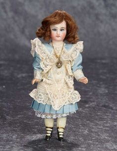 Solid domed bisque socket head with flat-cut neck socket, blue glass eyes, painted lashes, closed mouth with center accent line, pierced ears, brunette human hair, composition five-piece body with neck dowel for attachment to head, painted stockings and three-strap ankle boots, nicely costumed. Sonneberg, circa 1882, mystery maker.
