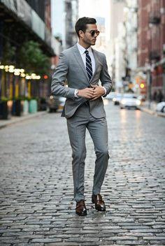business kleider eleganter grauer anzug weises hemd reirte krawatte braune schuhe braune sonnenbrille