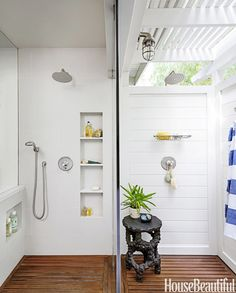 Only a glass wall separates the indoor shower on the left from the outdoor shower on the right for an uninterrupted visual flow of space in this Los Angeles bathroom designed by John De Bastiani. Fixtures by Jaclo. Outdoor light and soap dish by Restoration Hardware. Table from Dennis & Leen.   - HouseBeautiful.com