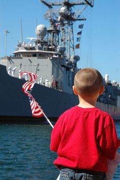 A young boy waves the flag in anticipation as guided-missile frigate USS Gary (FFG 51) pulls into port.