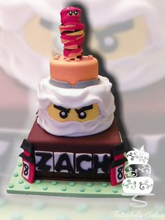 Lego Ninjago Cake, i would just do the nijago in white, and name bottom layer , and not do the stuff on top
