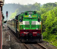 Green loco with green train, waving green flags in green surroundings. ERS hauled 12202 Kochuveli - Mumbai LTT Garib Rath Express crossing south bound 12432 Trivandrum Rajdhani Express at Savarda. Rajdhani Express, Indian Railway Train, Train Wallpaper, Rainy Window, Frame Gallery, Train Tour, Green Monsters, Indian Artist, Diesel Locomotive