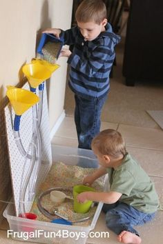Sensory play with rice and a pegboard with funnels and tubes. Super fun - and could use this in the summer with water!