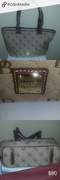Dooney & Bourke Small leisure Cloth bag with leather details. Feet on the bottom. Red interior.  Brand new without the tags. Excellent Condition. No stains or marks in or outside the bag. Has the signature DB  on it and zips up. 4 pockets on the inside. Dooney & Bourke Bags Shoulder Bags