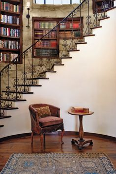 "LIBRARY STAIRCASE. ""An elliptical staircase rises from the wine cellar through a library of books set into niches in the curved stone wall."" Private Residence, Hilltop Villa, SAN ONOFRE DRIVE, Pacific Palisades, California. By KAA DESIGN, architecture & design firm,  and by CHRIS BARRETT DESIGN, Santa Monica, CA. http://www.chrisbarrettdesign.com/projects"