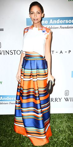Nicole Richie wearing Alberta Ferretti's flower-adorned crop top and multicolored stripe maxi-skirt, with a smattering of rings and a black clutch.
