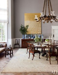 In the dining room of rug designer Ben Soleimani's Beverly Hills home, decorator Waldo Fernandez coated the walls in in a medium gray that helps diminish the vast scale of the room. Against one wall is a shimmering Rudolf Stingel painting, and a 1,500-pound 18th-century English chandelier hangs over the table | archdigest.com