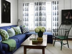 Big sectional sofa in navy blue color with wooden table and green chair in a white living corner decorated by black paintings and sheer curtain