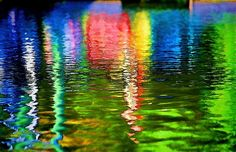 Reflections of colorful Adirondack chairs on a river in Florida.