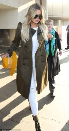 Belt up: Dressed in all-white, the 30-year-old added a pop of colour with a khaki trench c...