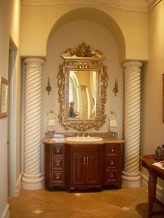 This bathroom is stunning....Beautiful floor, cast concrete columns, arches, lovely vanity and mirror.