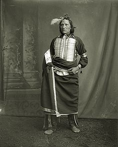 Oglala man Comes Out wearing a single feather in his hair and a hair pipe breastplate