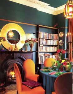 I love this dining room with deep peacock green walls and orange upholstered rust dining chairs