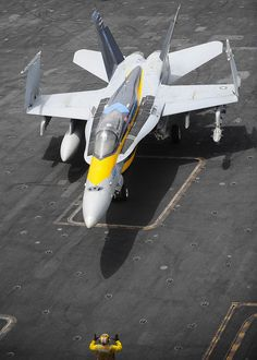 """U.S. 5TH FLEET AOR (Aug. 15, 2013) An F/A-18C Hornet assigned to the """"Blue Diamonds"""" of Strike Fighter Squadron (VFA) 146 is directed across the flight deck of the aircraft carrier USS Nimitz (CVN 68). Nimitz Strike Group is deployed to the U.S. 5th Fleet AOR conducting maritime security operations, theater security cooperation efforts and support missions for Operation Enduring Freedom. (U.S. Navy photo by Mass Communication Specialist 3rd Class Chris Bartlett/Released)"""