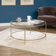 Muted gold and glass combine in the round to bring sleek style to any room. Smoothly finished on all sides and featuring a safety tempered glass top. Features: Safety tempered glass top Metal construction Finished on all sides for versatile placement This product requires assembly