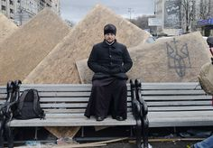 EuroMaidan; Kyiv, Ukraine 2013 - An Orthodox priest sits on a bench at Kyiv's Independence Square.