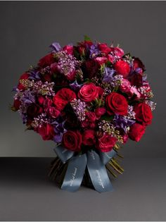 Wild At Heart - Nikki's passionately in love bouquet - The Passionately in Love bouquet combines a beautiful rich colour palette of red, deep pink and lilac using velvety black baccara roses, luxurious Paris roses, deep pink cheerio roses with scented lilac, creating a beautiful gift for a loved one this Valentine's Day.
