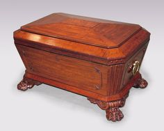 A fine early 19th Century Regency period fiddleback mahogany and ebony strung sarcophagus shaped Wine Cooler, having centre panelled mitred top above beaded canted corner panelled base retaining original brass carrying handles ending on well carved lions paw feet with scroll corner brackets.  Circa: 1820