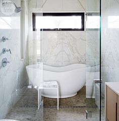 """Placing a stand-alone tub inside an open shower is a great space saving technique and is a modern update on the standard shower-tub combo."""