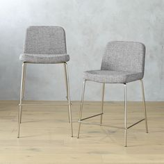"""high dining. Pull up a seat and stay awhile. Dapper stool dines comfy at counter height, upholstered in tweedy salt-and-pepper poly weave. Tailored trim with welt detail that traces rounded corners from curved shoulders to edge of seat. Tubular metal legs stand spare and sleek in polished nickel finish. Poly/cotton fabric: Salt and pepperPadded seat and back; bent plywood frameNickel-plated tubular metal legs24""""H seat sized for counters; 30""""H seat sized for barsMade in Taiwan."""
