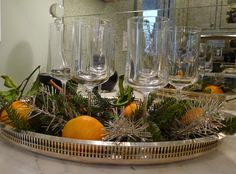 A silver drink tray ready for champagne or holiday cocktails to be served is adorned with holiday greenery, silver tinsel and real oranges at the Atlanta Christmas House 2012.