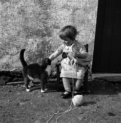 Girl seated with knitting, petting a cat. UK, 1939-46 © J. Peterson