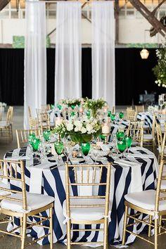 Low centerpieces on striped tablecloths | @lauren_fair | Brides.com