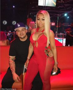 Flaunting it: Rob still sported his blue LA Dodger's hat, black coat and white t-shirt from their earlier excursion, while Blac Chyna appears far more casual than she did earlier in the club, when she flaunted her figure in a red jumpsuit (pictured)