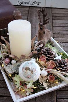 Hier ein Holztablett mit einer Stumpenkerze, verschiedenen Naturmaterialien, einer Weihnachtskugeln und dem dazugehörigem Rehlein. Auf der Deko liegt eine kleine Lichterkette die für die richtige...
