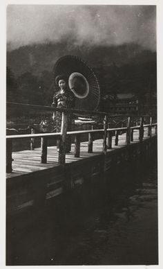 A snapshot photograph of a Japanese woman crossing a bridge, taken by an unknown photographer in about 1925. S)
