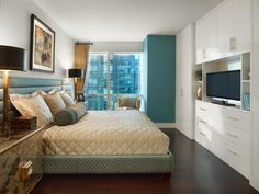 This bedroom looks sleek with white built-in cabinets and a plush quilted bedspread, but an infusion of cool aqua on one wall and in the bed frame takes the space to the next level. Dark hardwood floors and gold mirrored nightstands complete the design.