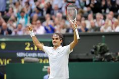 Roger Federer raises his arms in celebration after defeating Novak Djokovic in the semi-finals. - Matthias Hangst/AELTC