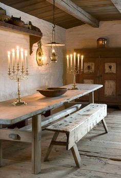 Old fashioned room lit by gold multi candle stick pieces, old wood + natural tones