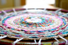 Hoop Dreams.   This is made with a Hula Hoop..after reviewing the authors notes it's recommended to down size to a smaller round such as an embroidery hoop to make the project time friendly for younger children. Large hula hoop makes a rug...small makes a trivet/hot pad.
