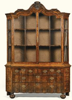 A Dutch walnut and burr walnut 'porseleinkast' or display cabinet, circa 1740 with a scrolled acanthus leaf carved cresting above two glazed doors enclosing two serpentine later gilded shelves with canted stiles each with five short drawers, above two short and two long drawers, with later pierced brass mounts, on bun feet Sotheby's