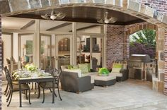 Beneath a large stone brick arch, we see this sprawling outdoor kitchen space, replete with grey rattan sectional, tile-topped dining table, and full cooking apparatus at right.