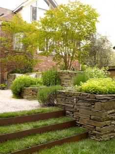corten stairs and retaining wall. Here's an example of corten used with grass and rock.  I think it works well together.  And the character of the house is traditional.