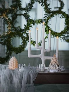 The white IKEA STRÅLA candelabra on a table in front of festive wreaths. The white IKEA STRÅLA candelabra on a table in front of festive wreaths.