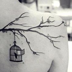 Tree branch and birdcage shoulder blade tattoo