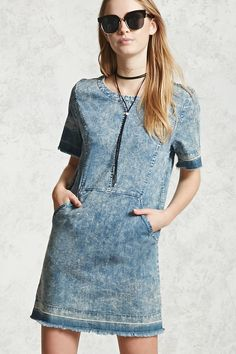 A denim dress featuring an acid wash fabric, round neck, short sleeves with frayed edges, front slip pockets, a back zipper closure, and a frayed hem.