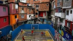 People take part in a football match held at the Tavares Bastos slum in Rio de Janeiro, Brazil